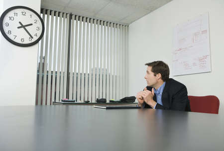 Businessman looking at a clock in an office