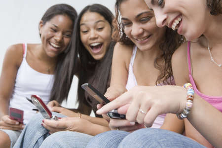 human entertainment: Four teenage girls using mobile phones Stock Photo