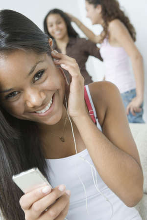 Portrait of a teenage girl listening to music with an MP3 player and smiling