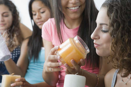 Four teenage girls playing with scented candles