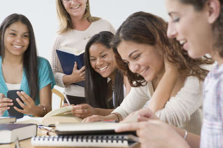 Four teenage girls studying with a teacher standing beside them