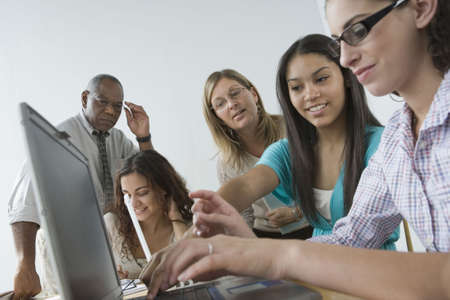 supportive: Three teenage girls working on a laptop with their teachers looking at them Stock Photo