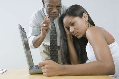 instructing: Male teacher instructing his student sitting in front of a laptop Stock Photo