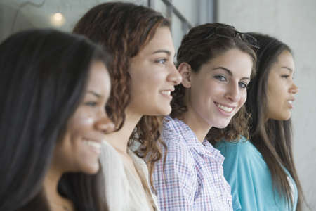 Portrait of a teenage girl smiling with her friends beside her