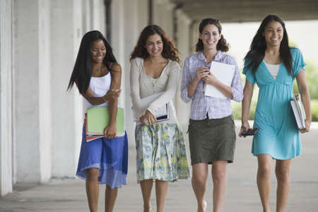 Portrait of four teenage girls holding books and hanging out in the school campus photo