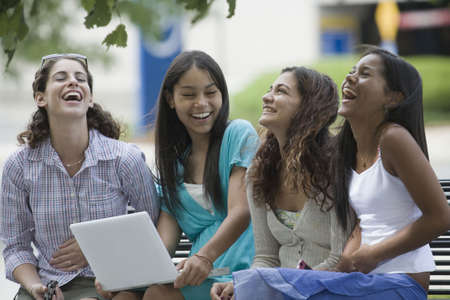 Four teenage girls sitting on a bench and smiling in the school campus Stock Photo - 5975718