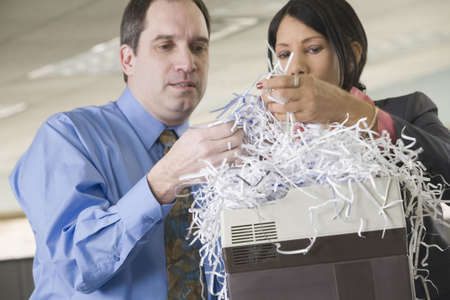 Close-up of a businessman and a businesswoman looking at shredded papers Stock Photo