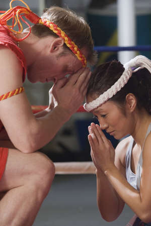 Woman and male instructor preparing for martial arts ceremonial exercise.