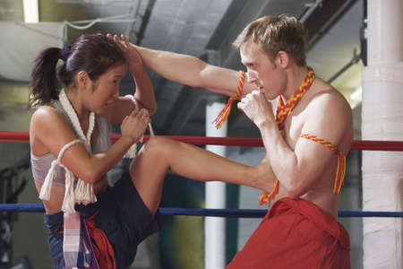 Man and woman in oriental Wei Kru martial art exercise with kick. Stock Photo