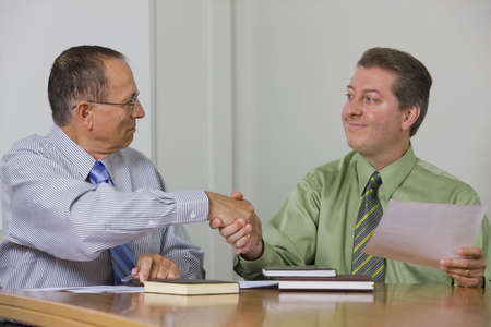 Two executives shaking hands during a business meeting over documents.