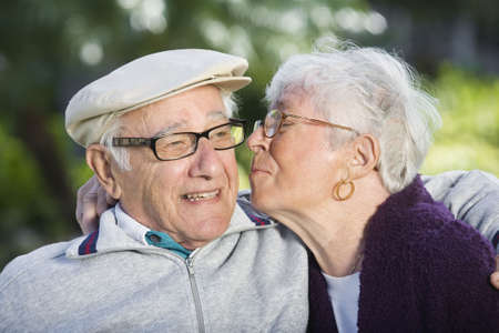 Senior woman kissing senior man on the cheek. Horizontally framed shot. Stock Photo