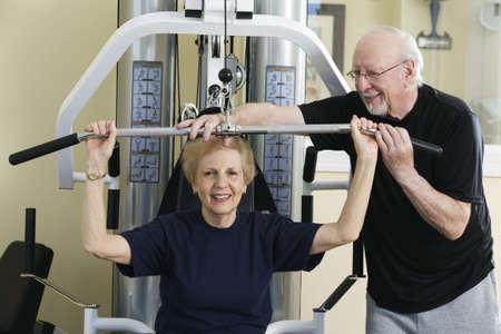 Senior couple exercising in the gym. Horizontally framed shot.
