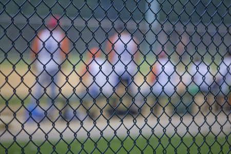 player bench: Closeup of chain link fence around baseball field. Horizontally framed shot.