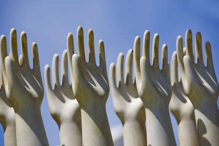 human likeness: Sculptured hands raised towards the sky. Horizontally framed shot.