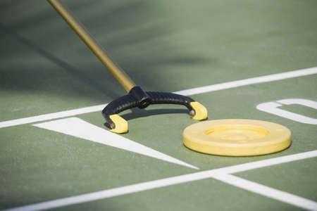 Close-up of a shuffleboard disc and shuffleboard cue