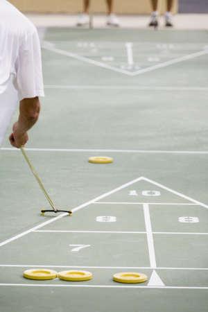 Senior man playing shuffleboard
