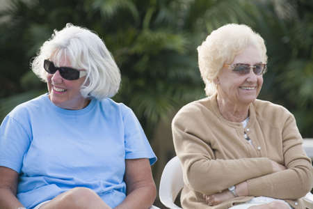 Two senior women sitting together and smiling