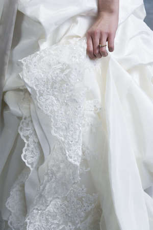 Midsection of bride wearing wedding gown. Stock Photo