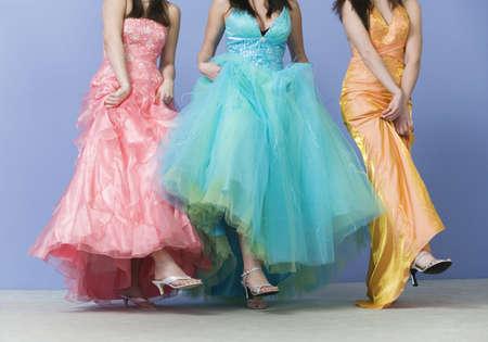 Mening van vrienden die dragend promkleding dansen.