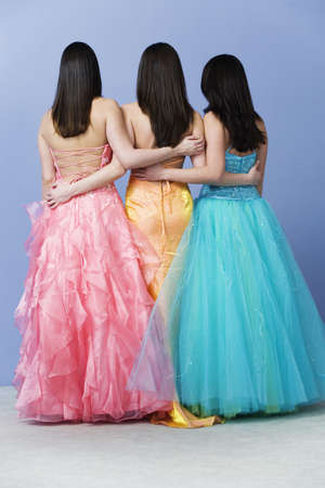yellow dress: View of friends holding  each other by the waist wearing prom dresses.