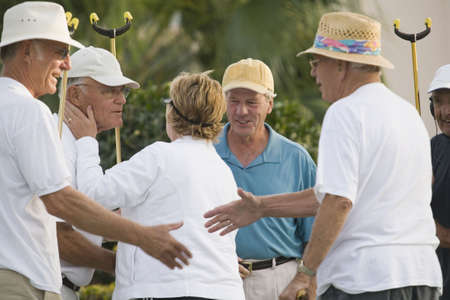 Senior people congratulating their friends after shuffleboard win