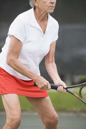 Senior woman playing tennis photo