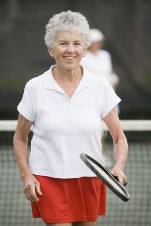 Portrait of a senior woman playing tennis and smiling photo