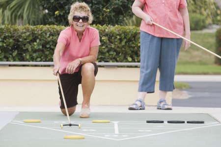 Two senior women playing shuffleboard Stock Photo