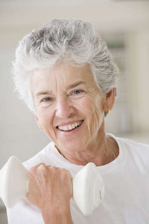 Portrait of a senior woman exercising with a hand weight photo