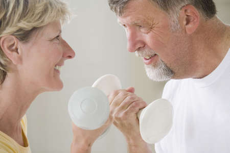 Close-up of a senior couple holding hand weights and smiling photo