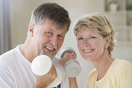 Portrait of a senior couple exercising with hand weights and smiling photo