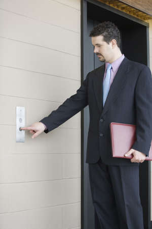 Businessman pressing button for elevator in an office building Banco de Imagens