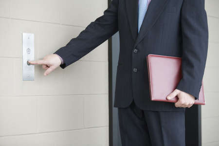 people in elevator: Mid section view of a businessman pressing button for elevator in an office building Stock Photo