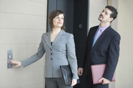Businesswoman pressing button for elevator in an office building with a businessman standing beside her