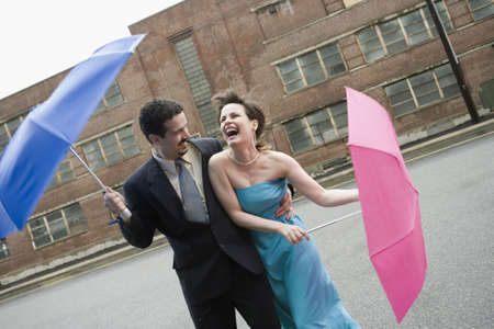 Mid adult couple holding umbrellas in a windy day and laughing photo