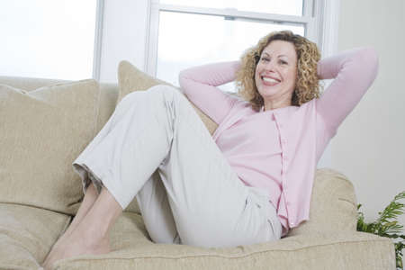 woman on couch: Portrait of a cheerful woman leaning on the couch.
