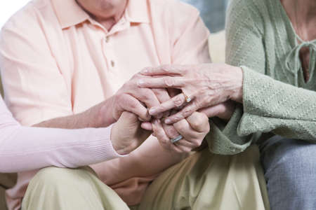 caring: View of friends holding hands together.