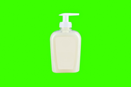 Hand sanitizer in plastic bottle on green background