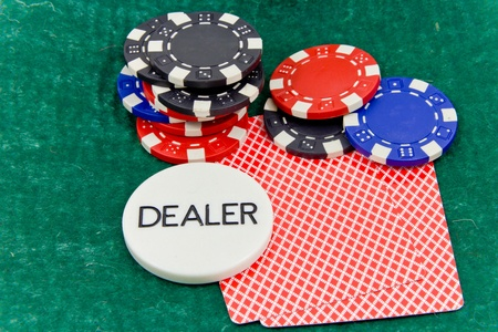 cards and stack of Poker chips and dealer button on a green background Stock Photo - 12121038