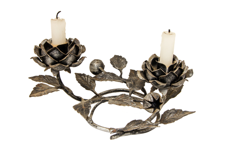 A cast iron candle holder with rose elements