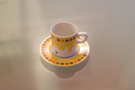 Yellow and white coffee cup decorated over a modern table Stock Photo