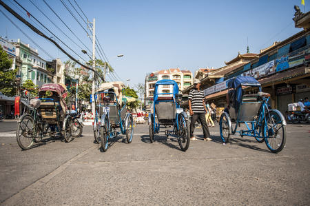 trishaw: HO CHI MINH CITY, VIETNAM - FEB 19:  A row of cyclos waits for tourist on FEb 19, 2010 in Saigon, Vietnam. Cyclo used to be a popular transportation in Vietnam.