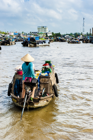 can tho: woman with concal hat driving her machine boat to floating market oon Mekong river