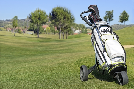 Golf Trolley in a golf course with a green background and blue sky photo