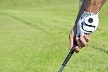 Hands holding a golf stick on of them with the glove in a blurred grass backgound photo