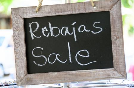 Rebajas sale writen in english and spanish in a chalkboard