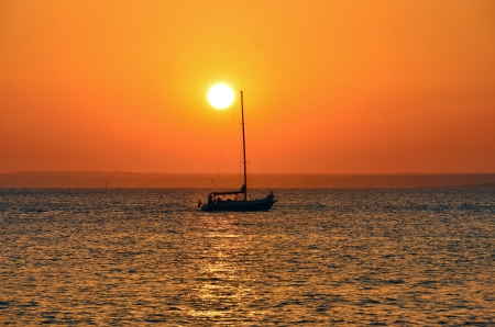 Sunset in the sea with a vessel and the reflections in the water