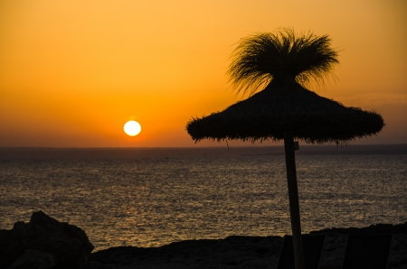 Sunset with a sunshade and the sea 免版税图像