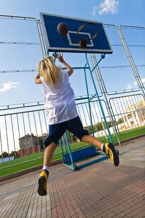 Young blond girl is playing basketball outside photo