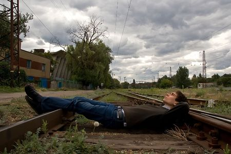 Young man laying on a railway tracks looking into the sky photo